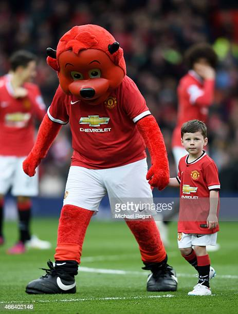 Kai Rooney son of Wayne Rooney of Manchester United is lead off the pitch by Fred the Red during the Barclays Premier League match between Manchester...