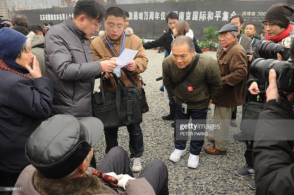 Kai Satoru (centre R), the son of a Japanese soldier who served in China, bows to a survivor (bottom L) at a ceremony for victims to mark the 75th anniversary of the Nanjing massacre at the Memorial Museum in Nanjing on December 13, 2012. Air raid sirens sounded in the Chinese city of Nanjing on December 13 as it marked the 75th anniversary of the mass killing and rape committed there by Japanese soldiers -- with the Asian powers' ties at a deep low. AFP PHOTO/Peter PARKS