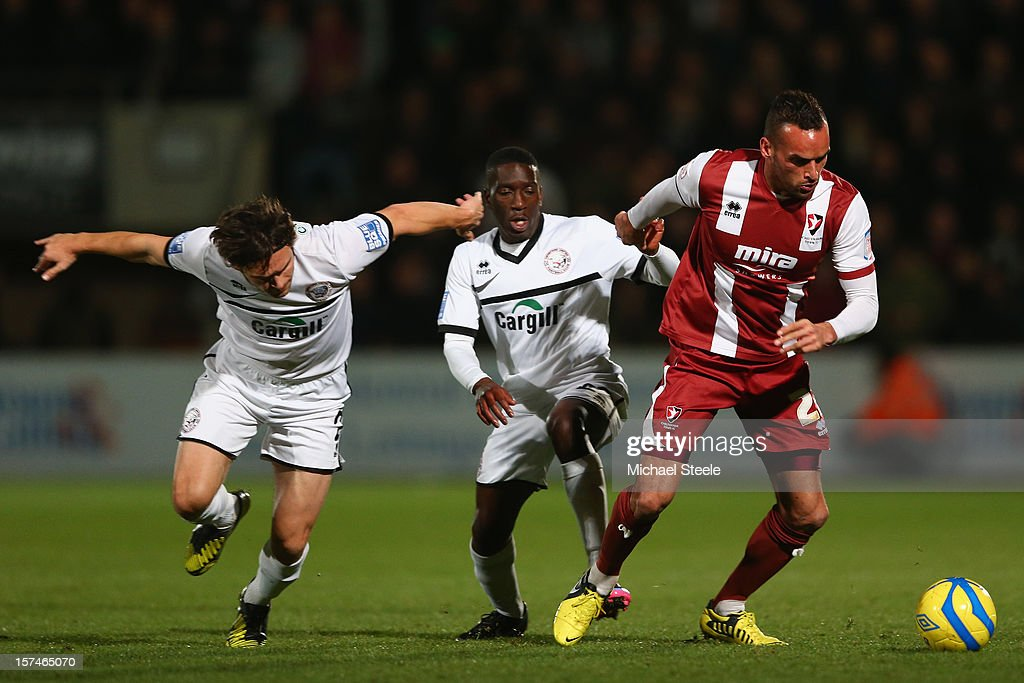 Kaid Mohamed (R) of Cheltenham Town is tracked by Brian Smikle (C) and Andy Gallinagh (L) of Hereford United during the FA Cup with Budweiser Second Round match between Cheltenham Town and Hereford United at the Abbey Business Stadium on December 3, 2012 in Cheltenham, England.