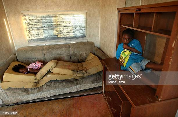 Kailah Smith 18 months sleeps on a moldy couch caused by rain leaks in her parents' trailer as Kimber Smith looks on just before the family moved out...