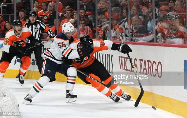 Kailer Yamamoto of the Edmonton Oilers battles for the puck behind his net against Valtteri Filuppula and Jori Lehtera of the Philadelphia Flyers on...