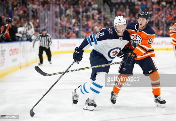 Kailer Yamamoto of the Edmonton Oilers battles Jacob Trouba of the Winnipeg Jets at Rogers Place on October 9 2017 in Edmonton Canada