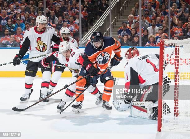 Kailer Yamamoto of the Edmonton Oilers looks for a shot against goaltender Mike Condon of the Ottawa Senators as Ottawa's JeanGabriel Pageau creates...