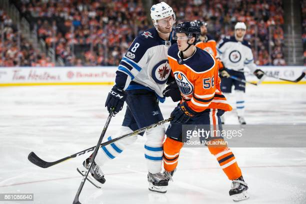 Kailer Yamamoto of the Edmonton Oilers takes a bump from Jacob Trouba of the Winnipeg Jets at Rogers Place on October 9 2017 in Edmonton Canada