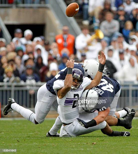Kain Colter of the Northwestern Wildcats is hit while attempting to make a catch against Glenn Carson and Stephon Morris of the Penn State Nittany...