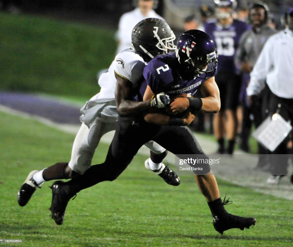 Kain Colter #2 of the Northwestern Wildcats is tackled by Ronald Zamort #7 of the Western Michigan Broncos during the third quarter on September 14, 2013 at Ryan Field in Evanston, Illinois.