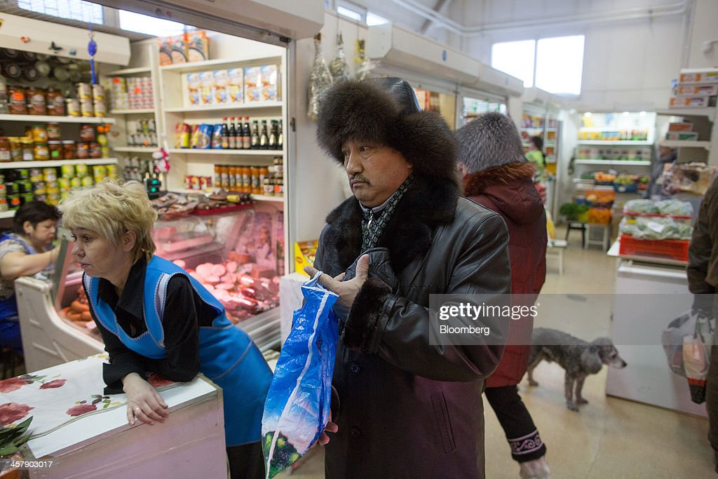 Kairat Zhakizhanov, a Kazakh mine worker, center, shops for provisions inside a general store in Udachny, Sakha Republic, Russia, on Saturday, Dec. 14, 2013. Russia plans to maintain control of Mirny-based Alrosa, which produces a quarter of the world's diamonds by value and more rough diamonds than De Beers by carat. Photographer: Andrey Rudakov/Bloomberg via Getty Images