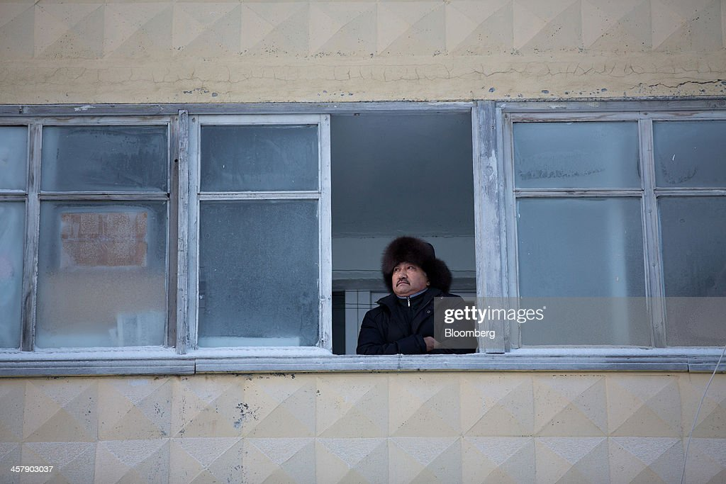 Kairat Zhakizhanov, a Kazakh mine worker, looks out from the window of his apartment in Udachny, Sakha Republic, Russia, on Saturday, Dec. 14, 2013. Russia plans to maintain control of Mirny-based Alrosa, which produces a quarter of the world's diamonds by value and more rough diamonds than De Beers by carat. Photographer: Andrey Rudakov/Bloomberg via Getty Images