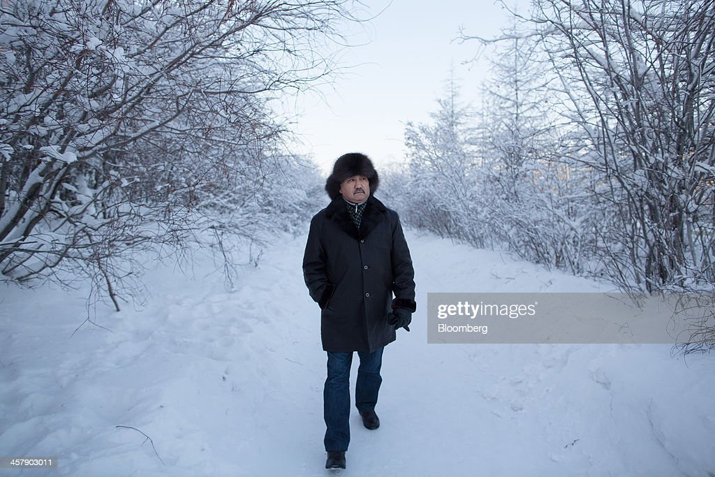 Kairat Zhakizhanov, a Kazakh mine worker, wears a sable fur hat as he walks along a frozen path past taiga forest in Udachny, Sakha Republic, Russia, on Saturday, Dec. 14, 2013. Russia plans to maintain control of Mirny-based Alrosa, which produces a quarter of the world's diamonds by value and more rough diamonds than De Beers by carat. Photographer: Andrey Rudakov/Bloomberg via Getty Images