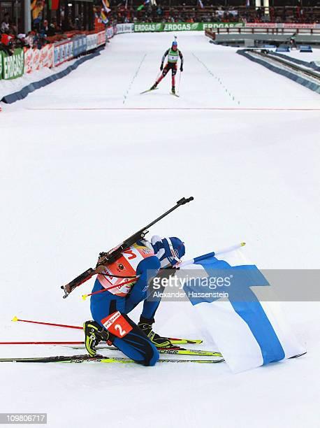 Kaisa Maekaeraeinen of Finland celebrates winning the gold medal whilst Magdalena Neuner of Germany finished the women's 10km pursuit during the IBU...