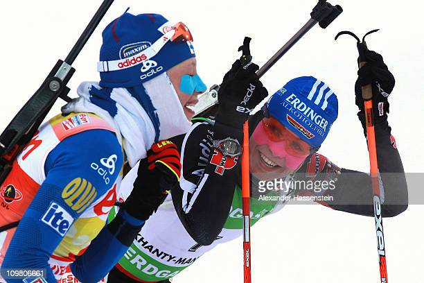 Kaisa Maekaeraeinen of Finland smiles at the finish area with Magdalena Neuner of Germany after winning the women's 10km pursuit during the IBU...