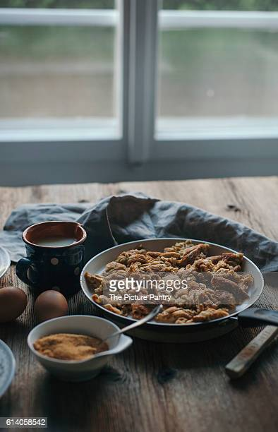 Kaiserschmarrn or shredded pancake in a pan on a rustic wooden table