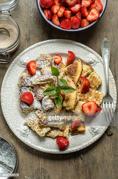 Kaiserschmarrn with fresh strawberries, cinnamon, powdered sugar and mint leaves on plate