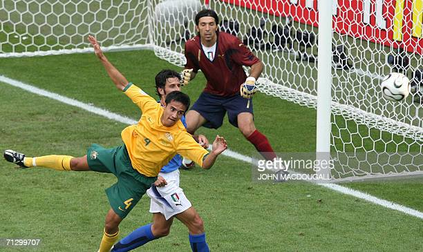 Australian midfielder Tim Cahill vies with Italian defender Fabio Grosso as Italian goalkeeper Gianluigi Buffon looks on during the round of 16 World...
