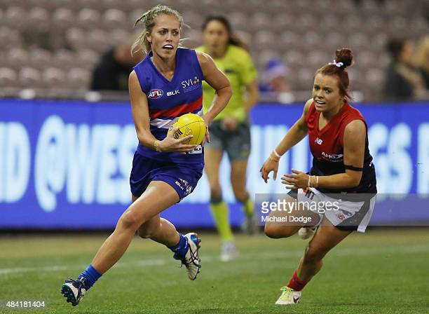 Kaitlyn Ashmore of the Bulldogs runs with the ball away from Brianna Green of the Demons during a Women's AFL exhibition match between Western...