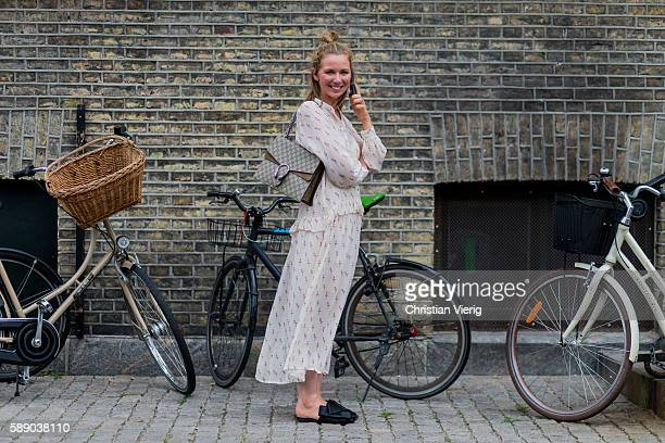 Kajsa Baekmark Mansson wearing a white dress with long sleeves slippers and a Gucci bag outside Revolver Fair during the third day of the Copenhagen...