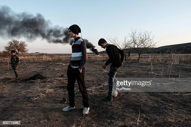 Kakais boys playing football and smoke seen behind in Tel Laban/ Gazakan on 30 December 2016 The Kakai Kurds are returning to their homes as Mosul...