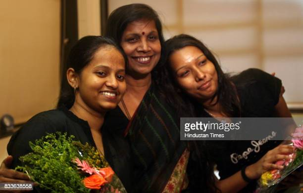 Kala Krishnan and Rosebud Gomes the commerce and MCVC toppers from NM College Vile Parle get bear hugged by their principal Sangeeta Kher