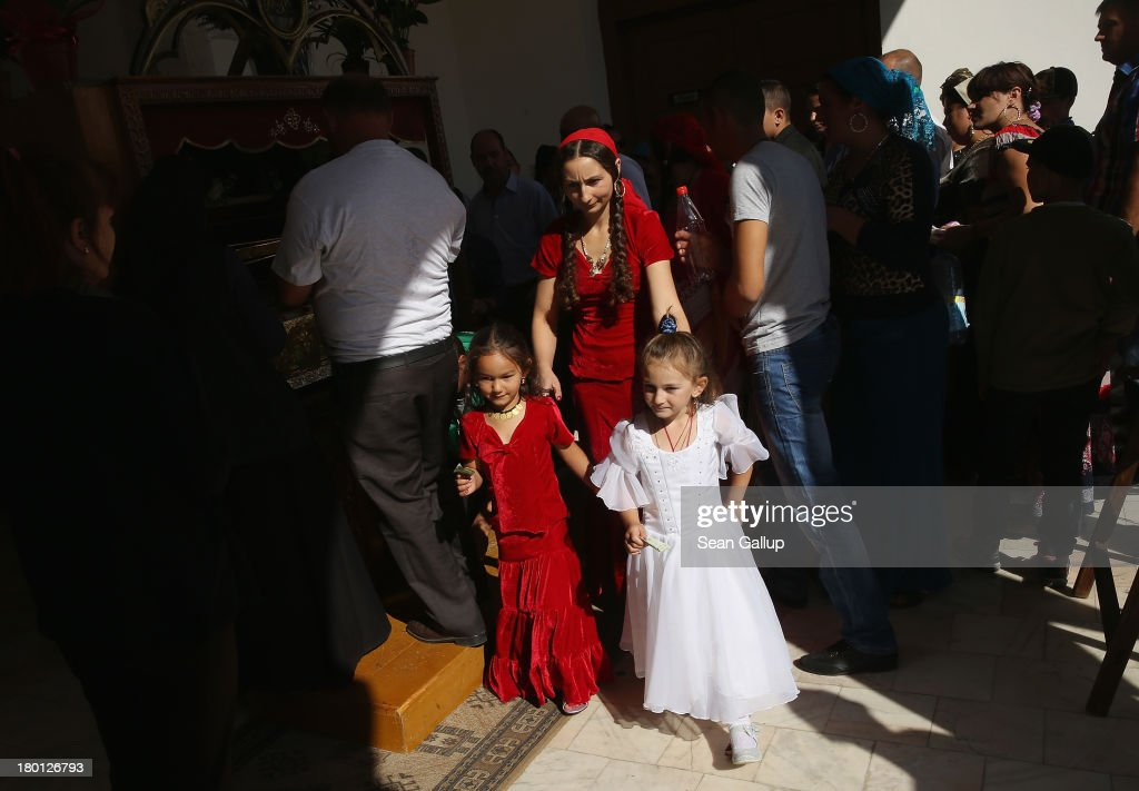 Kalderash Rom Bratiana Radulescu leads her daughters Gabriela (L), 5, and Irina, 6, after paying tribute and kissing the container of a relic of St. Gregory at the Bistrita monastery on September 8, 2013 in Bistrita, Romania. Every year thousands of Kalderash from across Romania arrive to visit the monastery and to gather at an open field nearby for a day or more of feasting, dancing, visiting and business dealing. Romania's Roma, many of whom call themselves tsigani, or Gypsies, are divided into different tribes that were once distinctive by their craft. The Kalderash were coppersmiths but today are known for dealing in scrap metal and metal products. Many Kalderash are among Romania's most traditonal and least assimilated Roma and most marry in their teens.