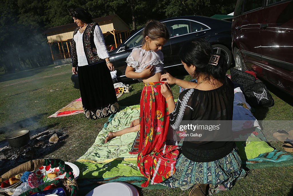 Kalderash Rom Maria 'Mercedes' Chiciu, 3, gets help from her mother Adelaida in putting on a dress at the field near the Bistrita monastery where thousands of mostly Kalderash Roma have gathered on September 8, 2013 in Bistrita, Romania. Every year thousands of Kalderash Roma from across Romania arrive to visit the nearby monastery to pay tribute to St. Gregory and to gather at the field nearby for a day or more of feasting, dancing, visiting and business dealing. Romania's Roma, many of whom call themselves tsigani, or Gypsies, are divided into different tribes that were once distinctive by their craft. The Kalderash were coppersmiths but today are known for dealing in scrap metal and metal products. Many Kalderash are among Romania's most traditonal and least assimilated Roma and most marry in their teens.
