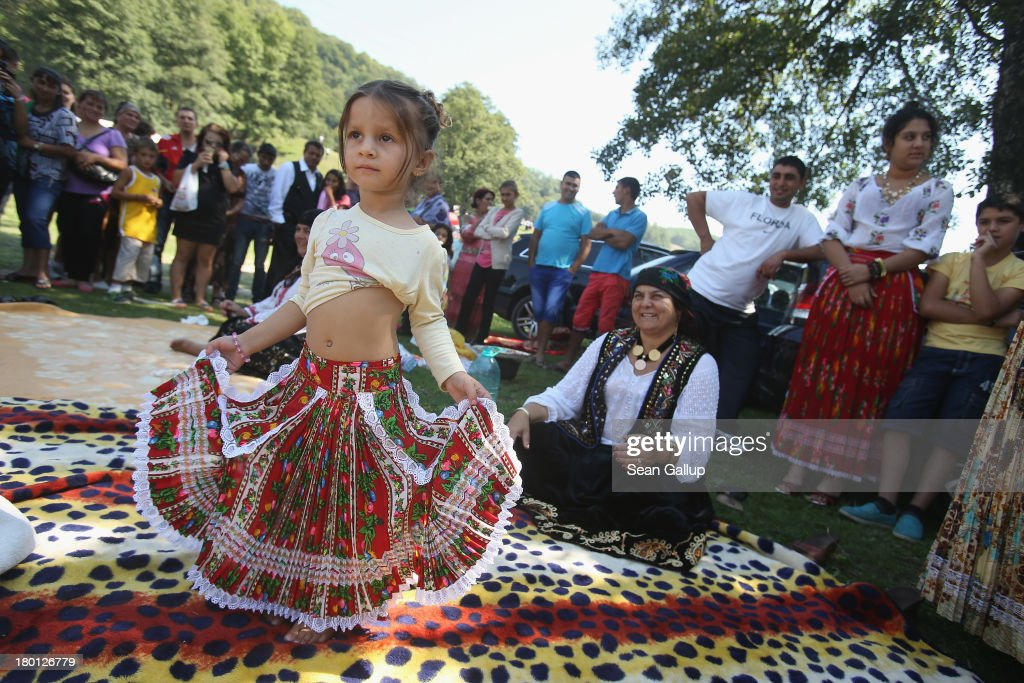 Kalderash Rom Maria 'Mercedes' Chiciu, 3, shows off her belly dancing skills as her grandmother Exspertiza Dumitru (sitting) looks on at the field near the Bistrita monastery where thousands of mostly Kalderash Roma have gathered on September 8, 2013 in Bistrita, Romania. Every year thousands of Kalderash Roma from across Romania arrive to visit the nearby monastery to pay tribute to St. Gregory and to gather at the field nearby for a day or more of feasting, dancing, visiting and business dealing. Romania's Roma, many of whom call themselves tsigani, or Gypsies, are divided into different tribes that were once distinctive by their craft. The Kalderash were coppersmiths but today are known for dealing in scrap metal and metal products. Many Kalderash are among Romania's most traditonal and least assimilated Roma and most marry in their teens.