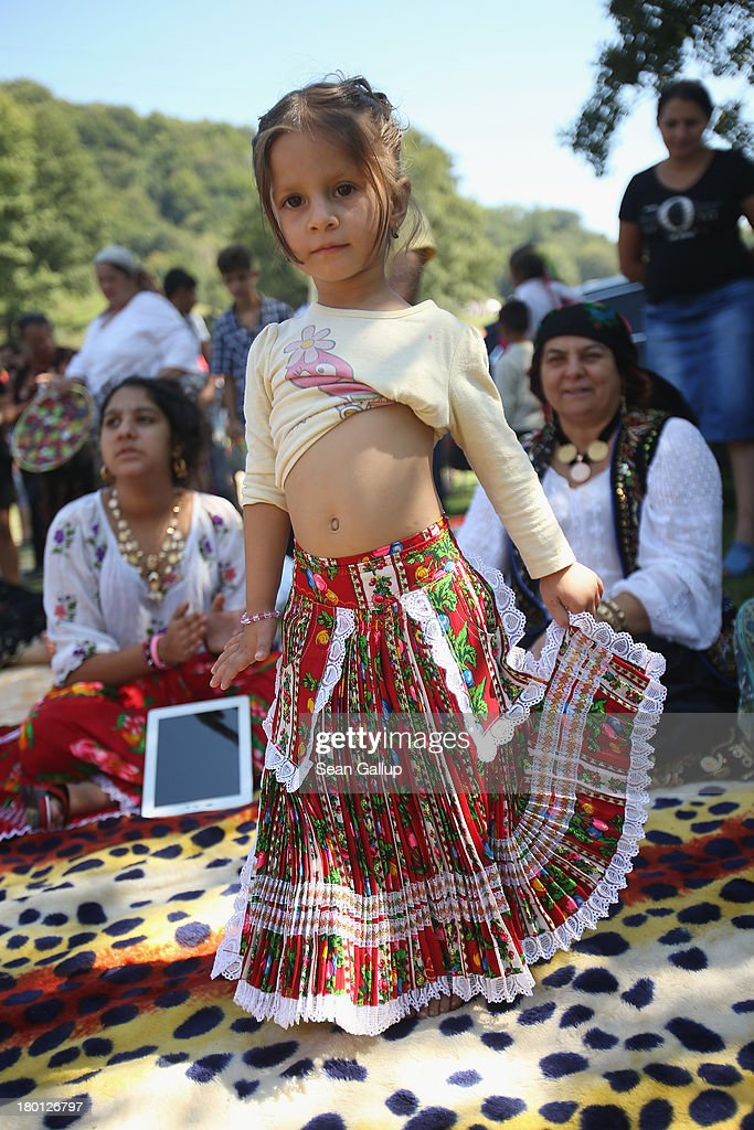 Kalderash Rom Maria 'Mercedes' Chiciu, 3, shows off her belly dancing skills while her grandmother Exspertiza Dumitru and sister Surprisa look on at the field near the Bistrita monastery where thousands of mostly Kalderash Roma have gathered on September 8, 2013 in Bistrita, Romania. Every year thousands of Kalderash Roma from across Romania arrive to visit the nearby monastery to pay tribute to St. Gregory and to gather at the field nearby for a day or more of feasting, dancing, visiting and business dealing. Romania's Roma, many of whom call themselves tsigani, or Gypsies, are divided into different tribes that were once distinctive by their craft. The Kalderash were coppersmiths but today are known for dealing in scrap metal and metal products. Many Kalderash are among Romania's most traditonal and least assimilated Roma and most marry in their teens.