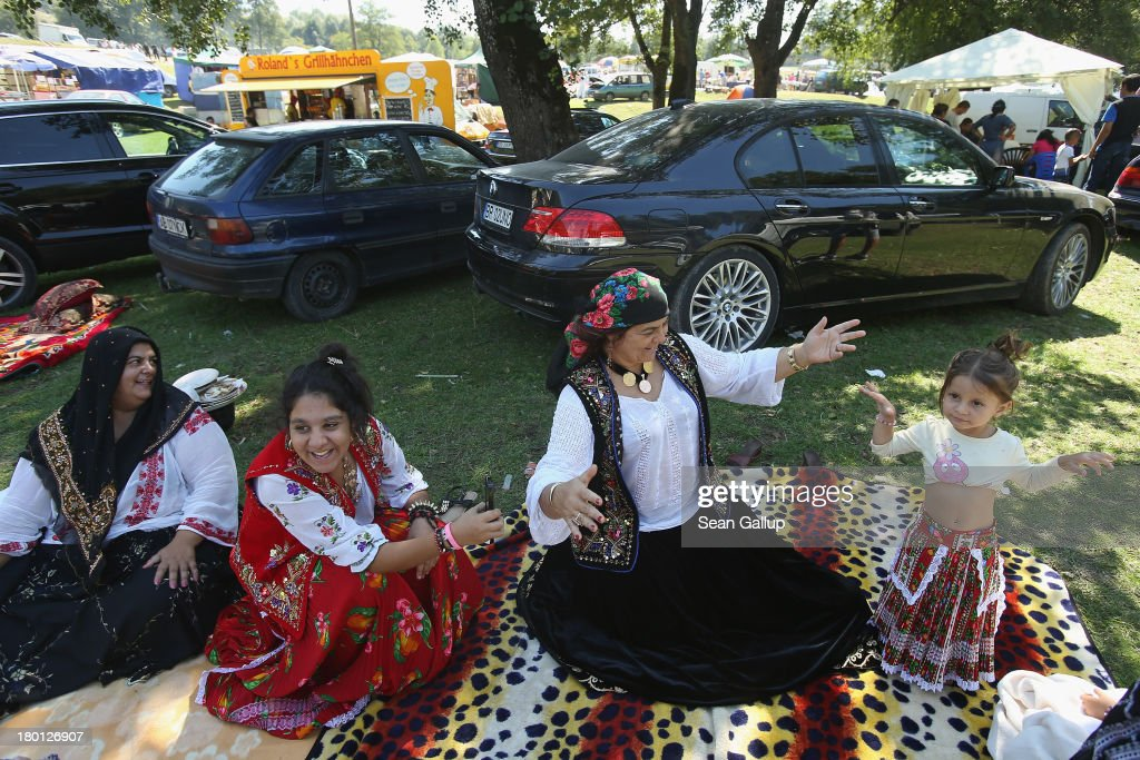 Kalderash Rom Maria 'Mercedes' Chiciu, 3, shows off her belly dancing skills while her grandmother Exspertiza Dumitru (2nd from R), sister Surprisa and other grandmother Mihaila Dimitrescu look on at the field near the Bistrita monastery where thousands of mostly Kalderash Roma have gathered on September 8, 2013 in Bistrita, Romania. Every year thousands of Kalderash Roma from across Romania arrive to visit the nearby monastery to pay tribute to St. Gregory and to gather at the field nearby for a day or more of feasting, dancing, visiting and business dealing. Romania's Roma, many of whom call themselves tsigani, or Gypsies, are divided into different tribes that were once distinctive by their craft. The Kalderash were coppersmiths but today are known for dealing in scrap metal and metal products. Many Kalderash are among Romania's most traditonal and least assimilated Roma and most marry in their teens.