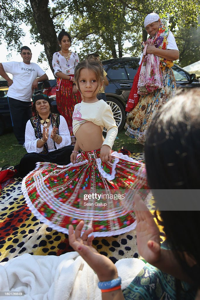 Kalderash Rom Maria 'Mercedes' Chiciu, 3, shows off her belly dancing skills to the applause of her grandmother Exspertiza Dumitru (L) at the field near the Bistrita monastery where thousands of mostly Kalderash Roma have gathered on September 8, 2013 in Bistrita, Romania. Every year thousands of Kalderash Roma from across Romania arrive to visit the nearby monastery to pay tribute to St. Gregory and to gather at the field nearby for a day or more of feasting, dancing, visiting and business dealing. Romania's Roma, many of whom call themselves tsigani, or Gypsies, are divided into different tribes that were once distinctive by their craft. The Kalderash were coppersmiths but today are known for dealing in scrap metal and metal products. Many Kalderash are among Romania's most traditonal and least assimilated Roma and most marry in their teens.
