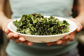 Kale salad in a white plate in a woman's hands