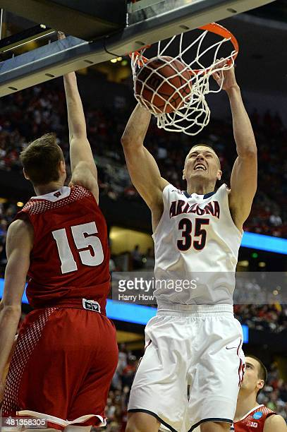 Kaleb Tarczewski of the Arizona Wildcats dunks the ball over Sam Dekker of the Wisconsin Badgers in the first half during the West Regional Final of...