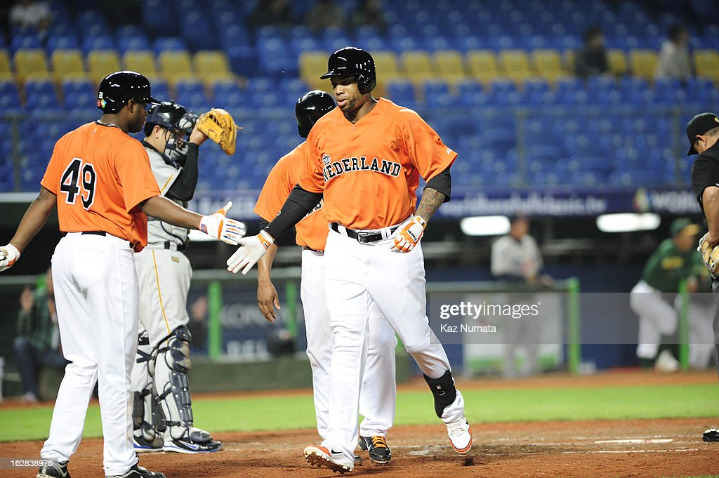 Kalian Sams #12 of Team Netherlands is greeted by teammate Dashenko Ricardo #49 after scoring a run during the World Baseball Classic exhibition game against the Industrial All-Star Team at Intercontinental Stadium on Tuesday, February 26, 2013 in Taichung, Tawain.