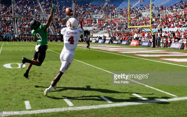 Kalib Woods of the Florida Atlantic Owls makes a reception in the red zone past Nate Brooks of the North Texas Mean Green during the Conference USA...
