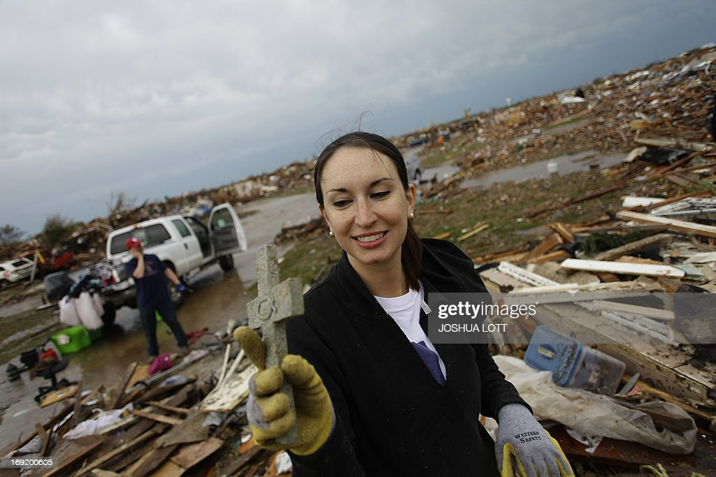 Kalissa Graham reacts after finding a cross in the the rubble of her destroyed home on May 21, 2013 in Moore, Oklahoma. Families returned to a blasted moonscape that had been an American suburb Tuesday after a monstrous tornado tore through the outskirts of Oklahoma City, killing at least 24 people. Nine children were among the dead and entire neighborhoods vanished, with often the foundations being the only thing left of what used to be houses and cars tossed like toys and heaped in big piles. AFP PHOTO/Joshua LOTT