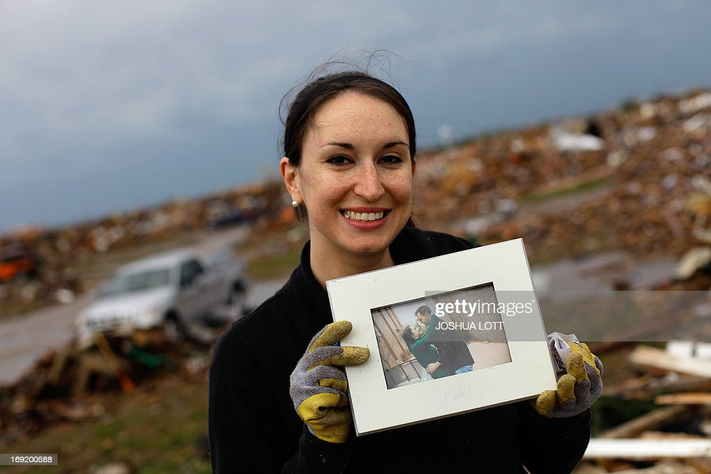 Kalissa Graham reacts after finding an engagement photo of her and her husband Roger Graham in the the rubble of her destroyed home on May 21, 2013 in Moore, Oklahoma. Families returned to a blasted moonscape that had been an American suburb Tuesday after a monstrous tornado tore through the outskirts of Oklahoma City, killing at least 24 people. Nine children were among the dead and entire neighborhoods vanished, with often the foundations being the only thing left of what used to be houses and cars tossed like toys and heaped in big piles. AFP PHOTO/Joshua LOTT
