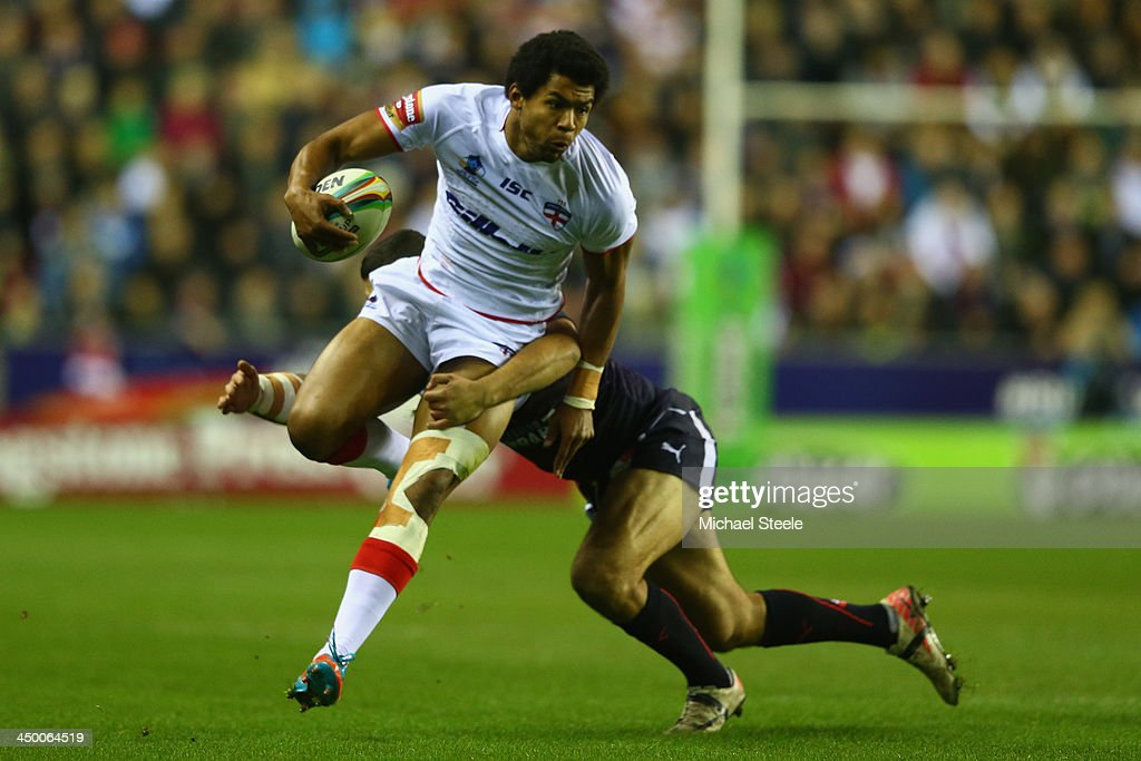 Kallum Watkins of England barges through the challenge of Sebastian Raguin of France during the Rugby League World Cup Quarter Final match between...