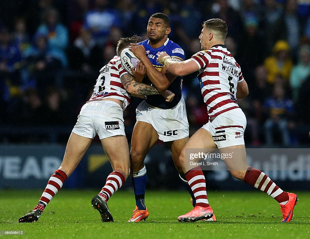 Kallum Watkins of Leeds Rhinos is tackled by George Williams and Josh Charnley of Wigan Warriors during the Round 2 match of the First Utility Super League Super 8s between Leeds Rhinos and Wigan Warriors at Headingley Carnegie Stadium on August 14, 2015 in Leeds, England.