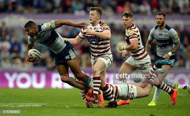 Kallum Watkins of Leeds Rhinos tackled by Connor Farrell and Dan Sarginson of Wigan Warriors during the Super League match between Leeds Rhinos and...