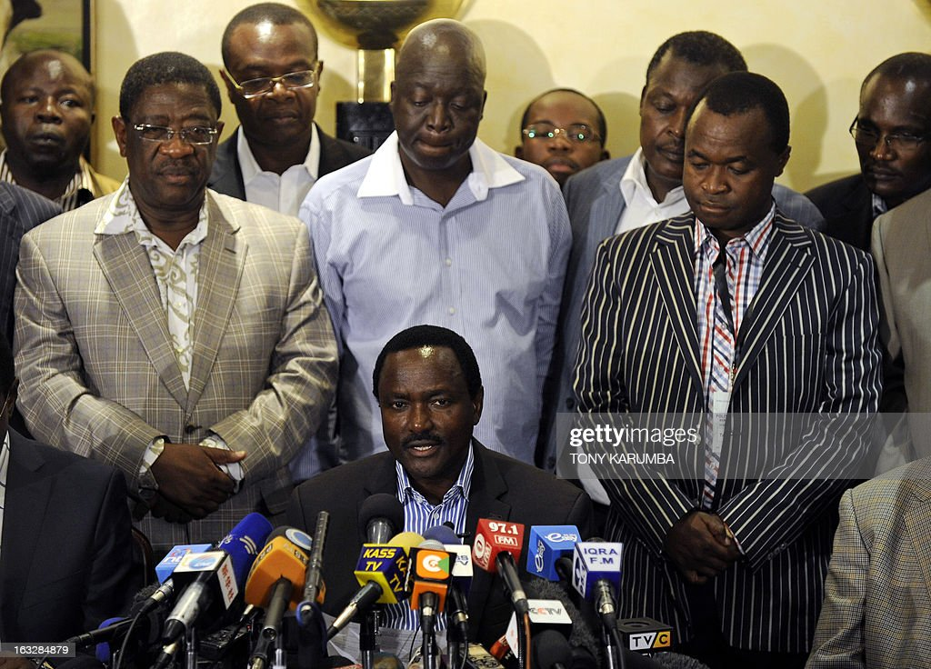 Kalonzo Musyoka (bottom), Kenya's outgoing vice president and running mate of CORD alliance's Presidential frontrunner Prime Minister Raila Odinga, gives a press conference flanked by other alliance members on March 7, 2013 in the Kenyan capital, Nairobi, at which he alleged that vote results had been 'doctored' and demanded a halt to vote counting. Musyoka also urged calm and stressed that his accusations about elections were 'not a call to mass action' and that the party was 'committed to the principle of rule of law'. AFP PHOTO / Tony KARUMBA