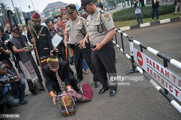Kalpataru environmental award winners from North Sumatra place their trophies in front of the presidential palace in Jakarta on September 3 2013 as...