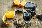 Kalua liqueur and pieces of dark chocolate and orange on a wooden table.