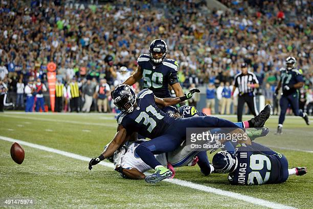 Kam Chancellor of the Seattle Seahawks forces Calvin Johnson of the Detroit Lions to fumble the ball near the goal line during the fourth quarter of...