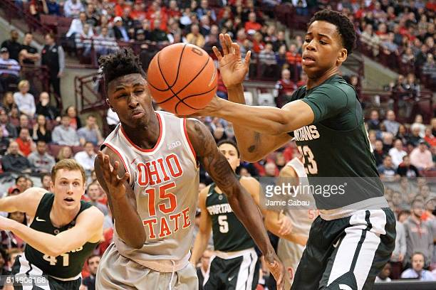 Kam Williams of the Ohio State Buckeyes and Deyonta Davis of the Michigan State Spartans battle for control of a loose ball in the first half on...