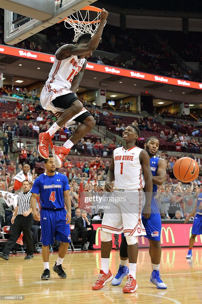Kam Williams of the Ohio State Buckeyes celebrates his alleyoop dunk in the second half against the MassachusettsLowel River Hawks with teammate...