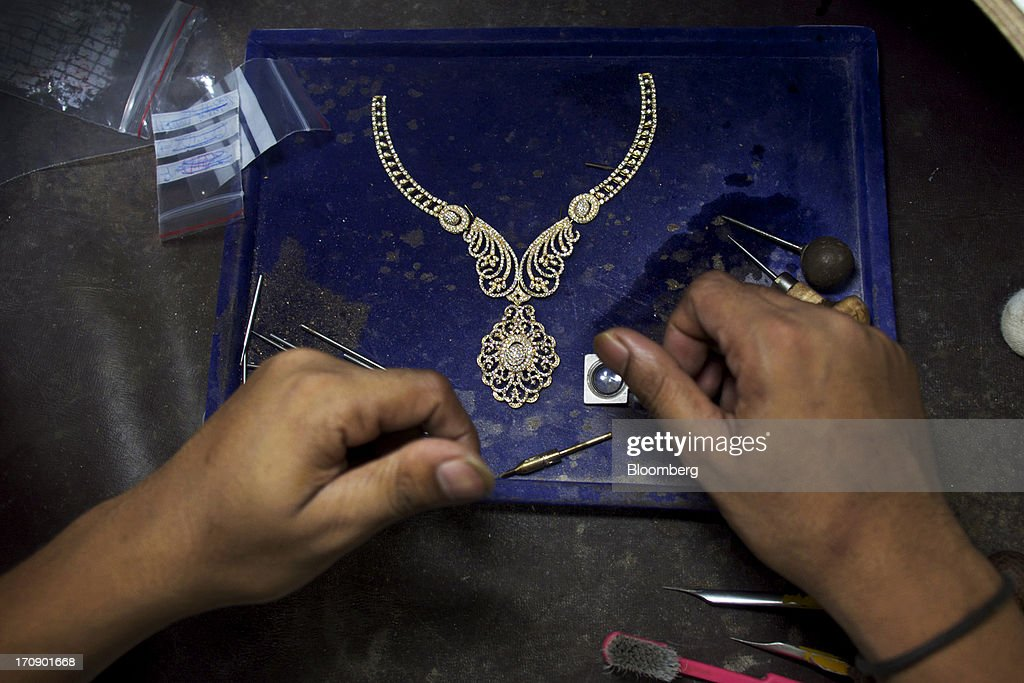A Kama Schachter Jewelry Pvt Ltd. necklace sits on a work bench at the company's diamond studded gold and platinum manufacturing facility in Mumbai, India, on Wednesday, June 19, 2013. India's exports of diamonds and gold jewelry grew 5.2% to $6.1 billion in April and May, says the Gem & Jewellery Export Promotion Council on June 18, 2013. Photographer: Adeel Halim/Bloomberg via Getty Images