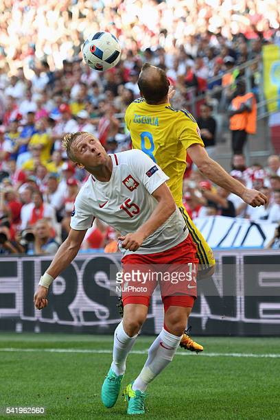 Kamil Glik of Poland and Roman Zozulya of Ukraine jump for the ball during the UEFA Euro 2016 Group C match between Ukraine and Poland at Stade...