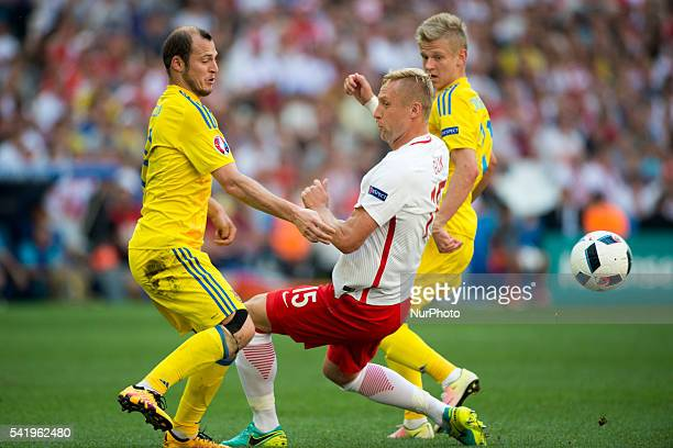 Kamil Glik of Poland fights for the ball with Roman Zozulya and Olexandr Zinchenko of Ukraine during the UEFA Euro 2016 Group C match between Ukraine...