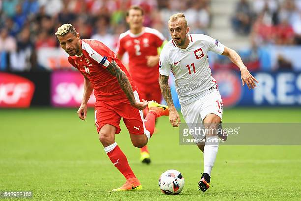 Kamil Grosicki of Poland and Valon Behrami of Switzerland compete for the ball during the UEFA EURO 2016 round of 16 match between Switzerland and...