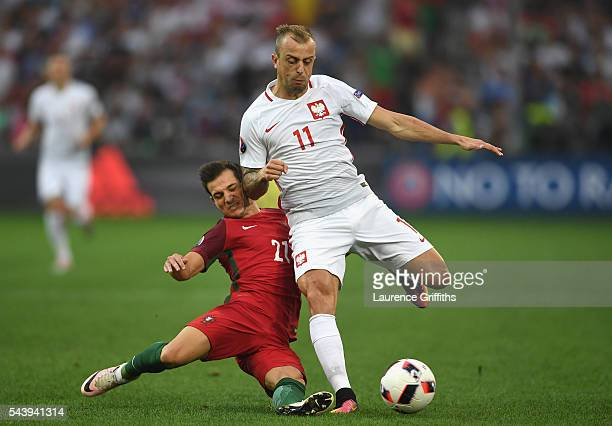 Kamil Grosicki of Poland is tackled by Cedric Soares of Portugal during the UEFA EURO 2016 quarter final match between Poland and Portugal at Stade...