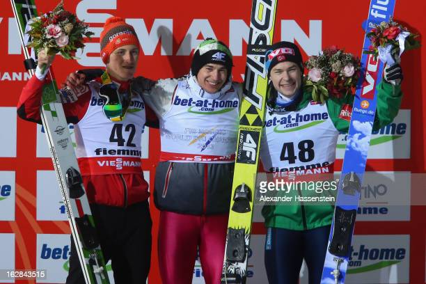 Kamil Stoch of Poland celebrates victory with second placed Peter Prevc of Slovenia and third placed Anders Jacobsen of Norway during the Men's Ski...