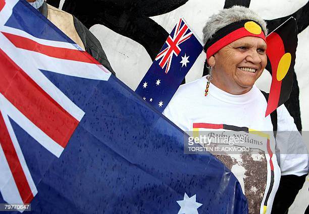 Kamilaroi Aborigine Joan Baker displays both the national flag and the Aboriginal flag as she watches Australian Prime Minister Kevin Rudd on a large...